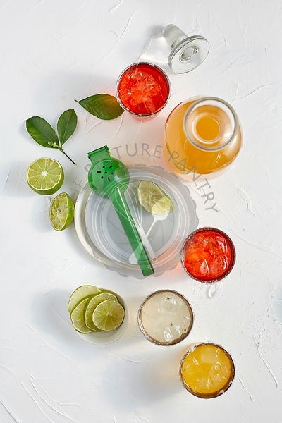Assorted flavors of Margaritas in glasses on a white surface with salt and limes