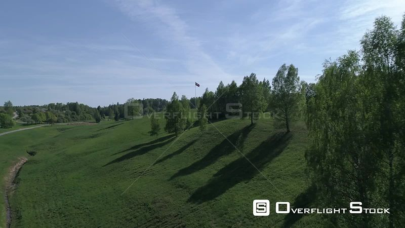 Aerial drone shot approaching a large flag of Latvia in green countryside and rolling hills