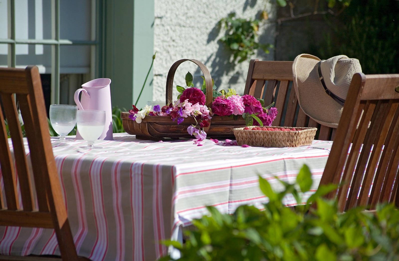 Blackdykes, North Berwick, East Lothian, Scotland, UK. cut flowers (roses & sweet peas), raspberries & lemonade on patio table