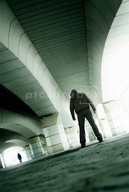 An atmospheric image of the hooded figure of a man following a woman under an arched bridge In Valencia.