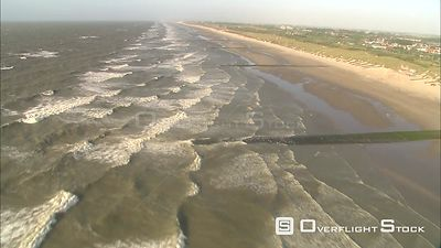 Above North Sea waves along the Belgian coast windsurfers briefly visible