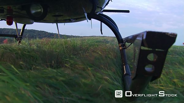 Fuselage-mount POV, helicopter landing in grass