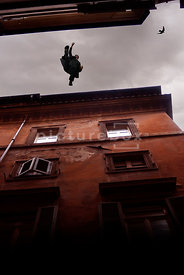 An atmospheric image of a mystery men jumping from one building rooftop to another in a chase in Rome, Italy.