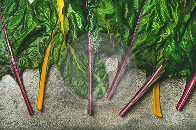 Flat-lay of fresh leaves of swiss chard over concrete stone background, top view