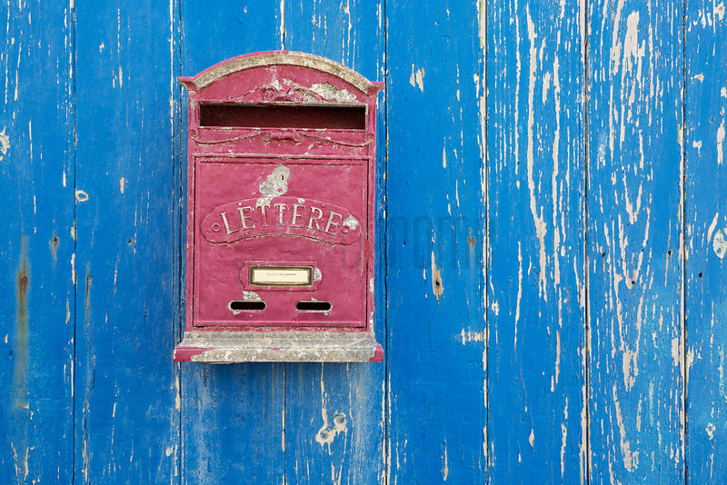 Red Mail Box Against a Blue Door