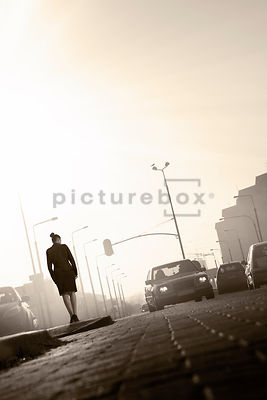 An atmospheric image of a mystery woman, watching a car driving towards her, in an urban setting.