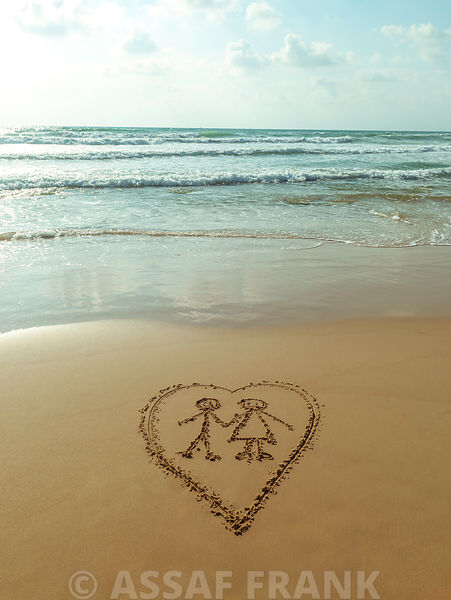 Couple in heart drawn on sand at the beach