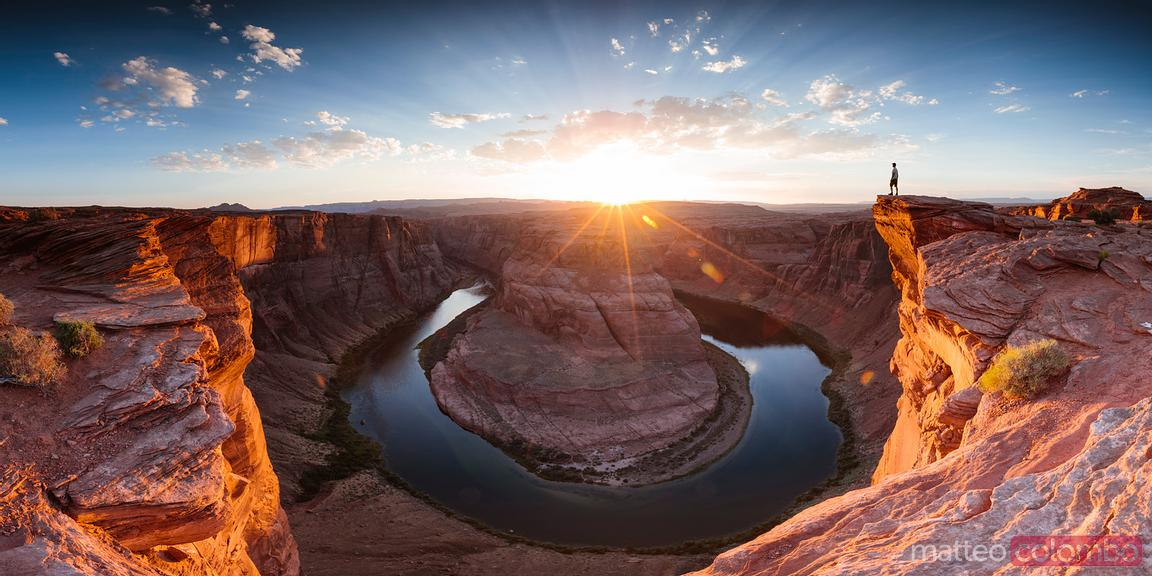 Man standing by horseshoe bend at sunset, USA