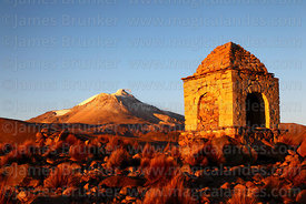Cairn on hilltop at sunset, Guallatiri volcano in background, Las Vicuñas National Reserve, Region XV, Chile