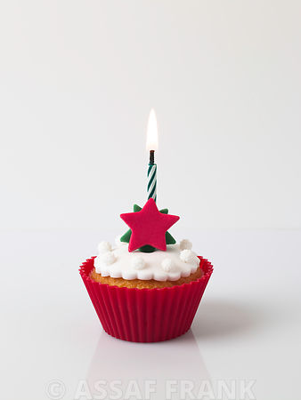 Cupcake with a star shaped docoration and a birthday candle
