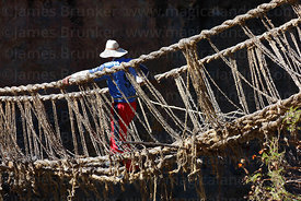 Man crosses old bridge with rope that will be used to pull the new foundation ropes across the canyon , Q'eswachaka , Canas p...