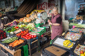 An elderly woman cleaning a spring onion on her stall in the Mercado do Bolhão, Porto, Portugal