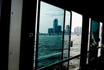 An atmospheric image of the view of New York City from a Liberty Island ferry's windows, with the reflection of a mysterious ...