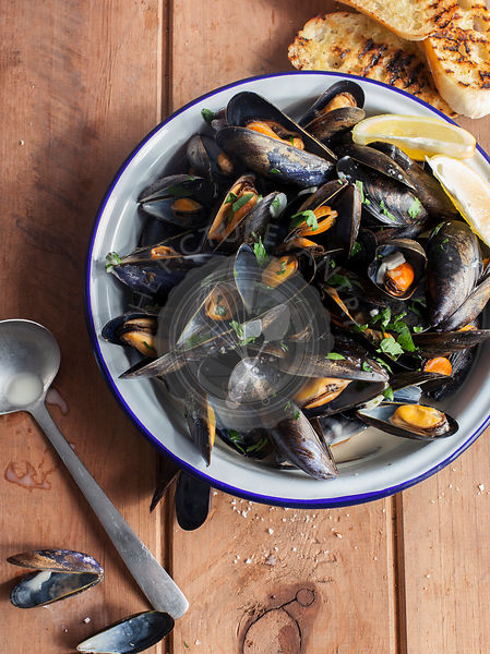 Bowl of Mussels in white wine and garlic on wooden background