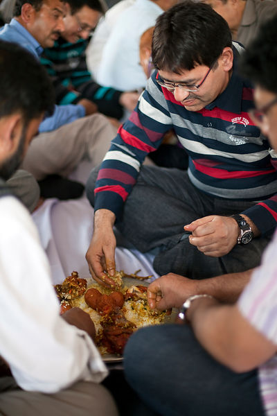 India - Srinagar - Male guests at a wedding party are served and eat a traditional Wazwan meal seated in groups of four aroun...