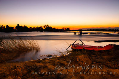 Empty red rubber raft on sandy beach at sunset, blurred water flowing in river