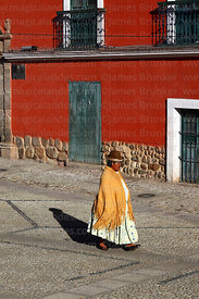 Aymara woman or cholita walking past Tambo Quirquincho museum building, La Paz, Bolivia