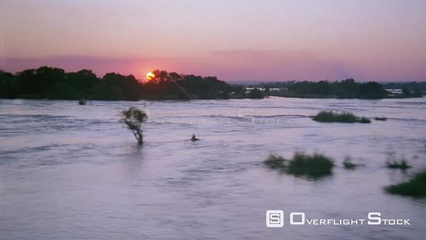 Aerial wide angle shot across flowing river with trees to land covered in trees and sun on horizon Botswana