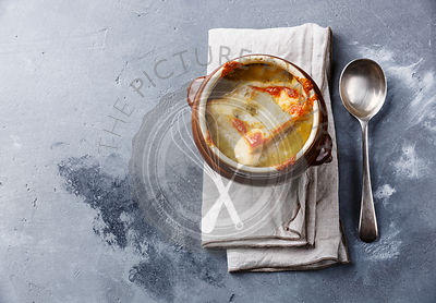 Onion soup with dried bread and cheddar cheese in bowl on concrete background copy space