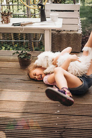 Happy girl playing with dog on wooden terrace
