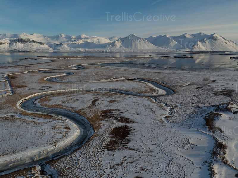 Aerial view of the snow covered mountains along the water in Borganes, Iceland