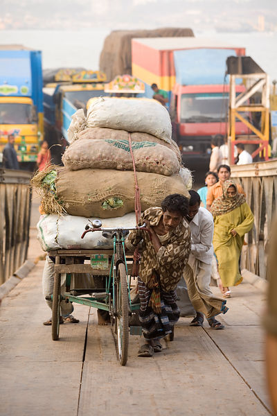 Bangladesh - Chittagong - A rickshaw driver pulls his heavy load up the gangplank after disembarking from a ferry on the sout...