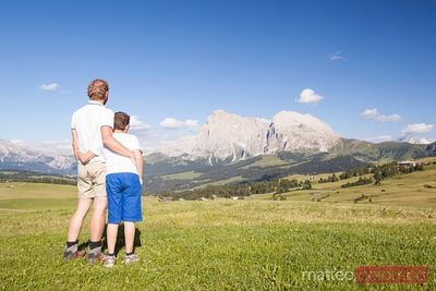 Dad and child looking at view on the Dolomites, Italy