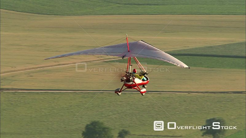 Midair view of an ultralight airplane and its pilot above rural fields, Belgium