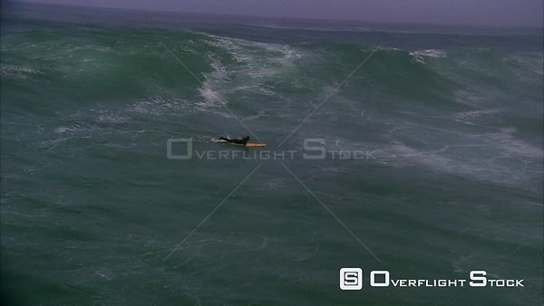 Aerial slow motion shot of a surfer lying on his surfboard paddling then getting up to ride the wave. Eastern Cape South Africa