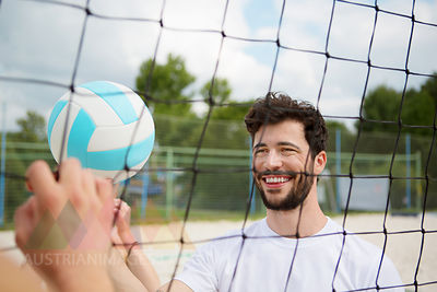 Smiling young man at net of beach volleyball field