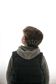 A mystery boy in a hoody and body warmer, looking up - shot from mid level.