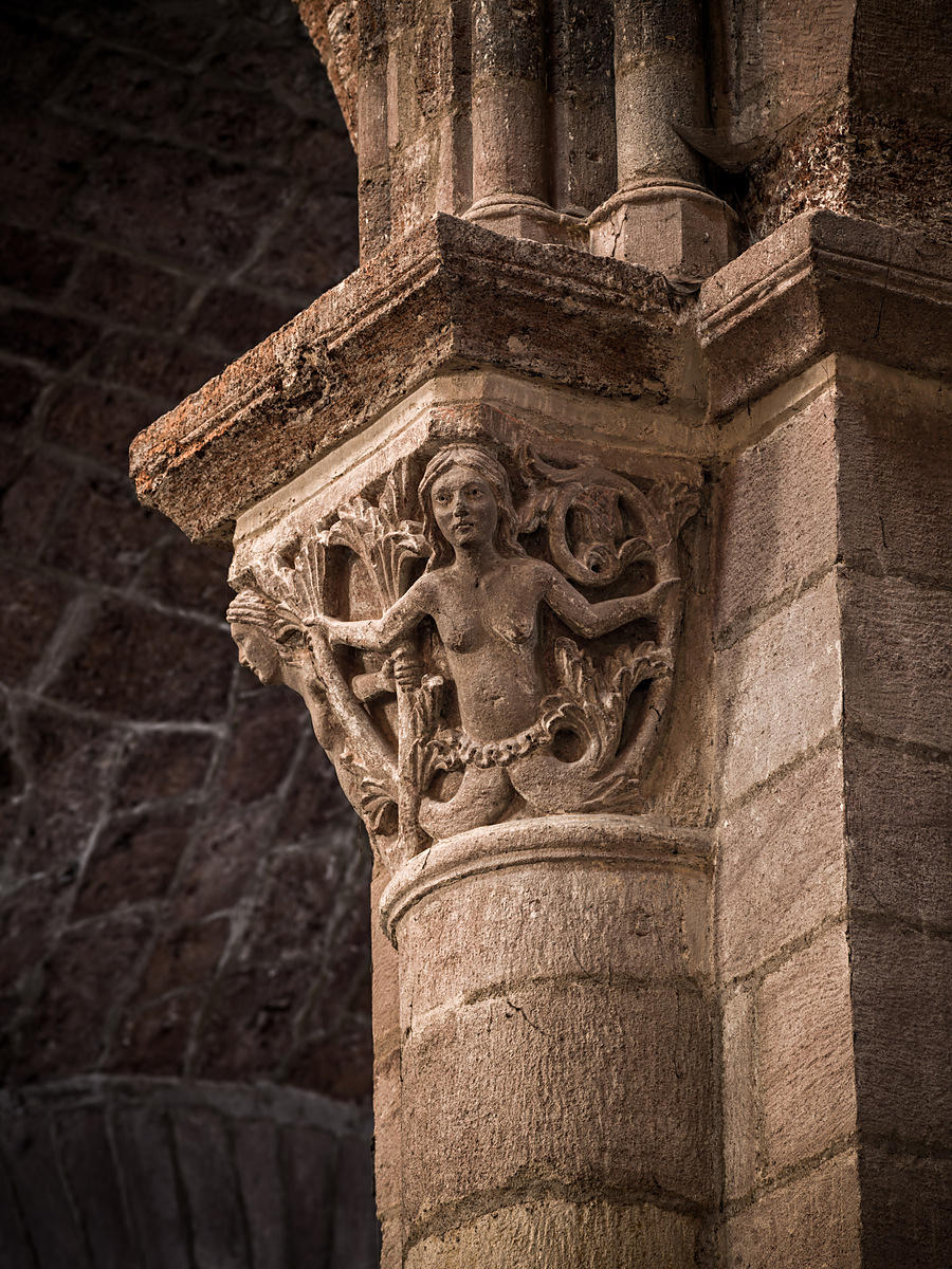 Capital of Brioude's basilica depicting a mermaid and Triton, Auvergne