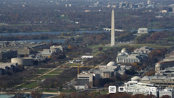 Wide view of the National Mall from Capitol Building to Lincoln Memorial. Airplane flies from right to left behind Washington...