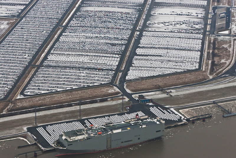 Aerial view of Emden Port, with boat at harbour and new cars for shipping overseas, East Frisia, Lower Saxony, Germany Februa...