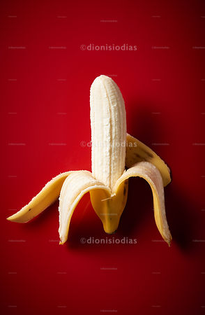 Peeled Banana on red background