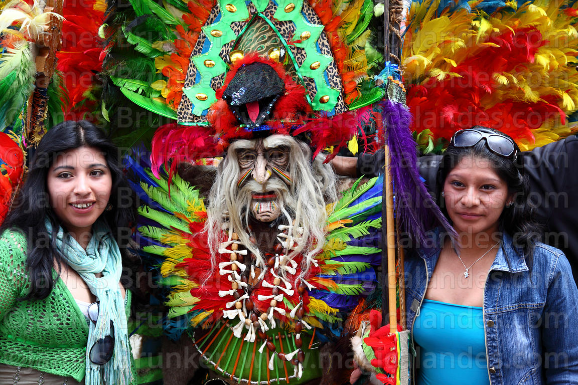 Girls having their photo taken with tobas dancer dressed as wizard / shaman, Oruro Carnival, Bolivia