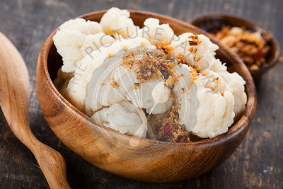 Steamed cauliflower with sauce in wooden bowl