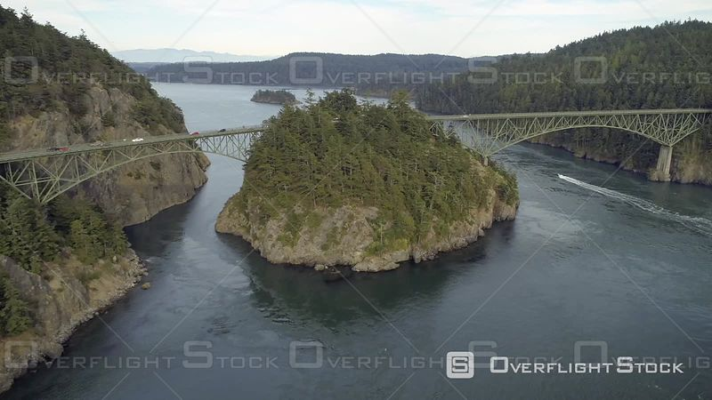 Ocean boat cruising under large Pacific Northwest bridge with cars driving. Deception Pass Washington USA