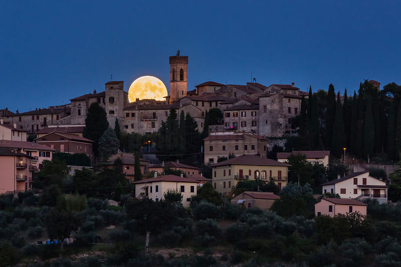 Full Moon Rising Behind Hill Town
