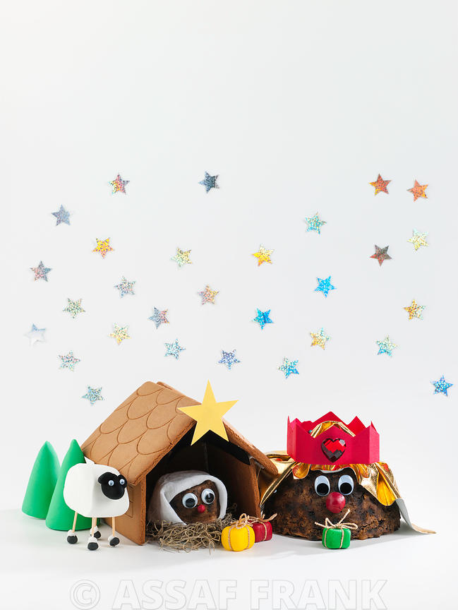 Nativity scene made of Christmas puddings on white background