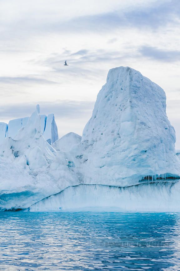 Tall iceberg in turquoise water in Ilulissat, Greenland