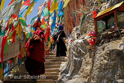 Buddhist pilgrims follow steps lined with prayer flags, painted rock carvings and shrines along the sacred Lingkhor circuit, ...