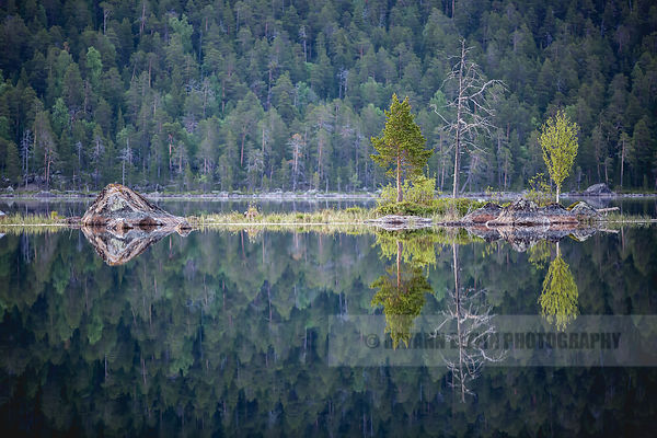 Perfect reflection of a small island on Ukonjärvi