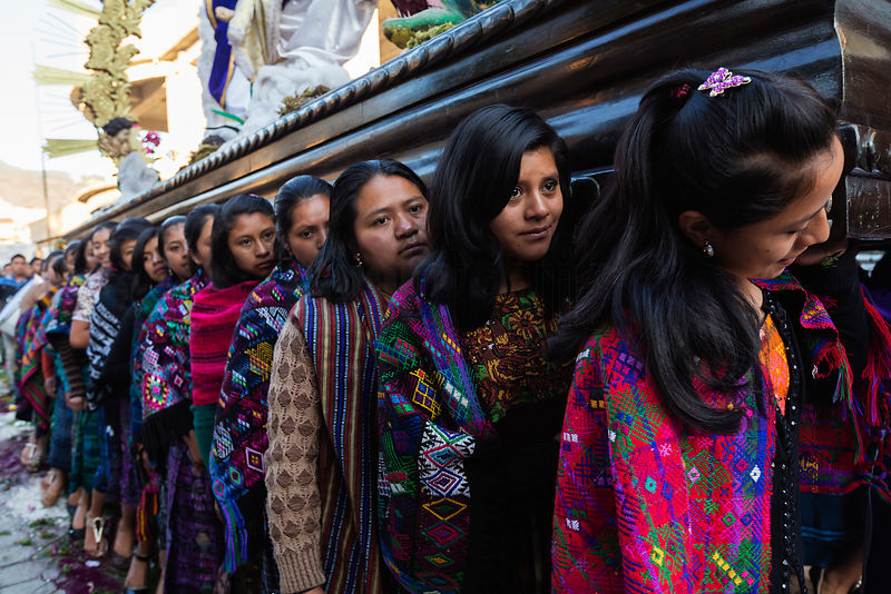 Young Women in Traditional Outfits Carrying Semana Santa Procession Float