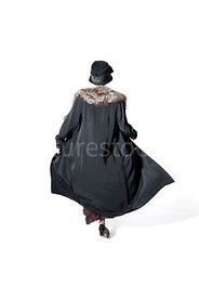 A vintage 1920s - 1930s woman in a long black coat, hat and fur running – shot from eye level.