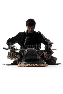 A western Samurai warrior sitting with his sword - shot from low-level.