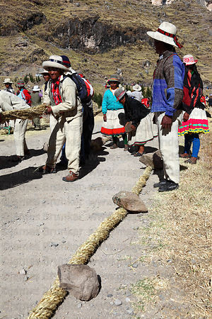 Men twisting the thin grass ropes together to make the thicker ropes for rebuilding the bridge, Q'eswachaka , Canas province ...
