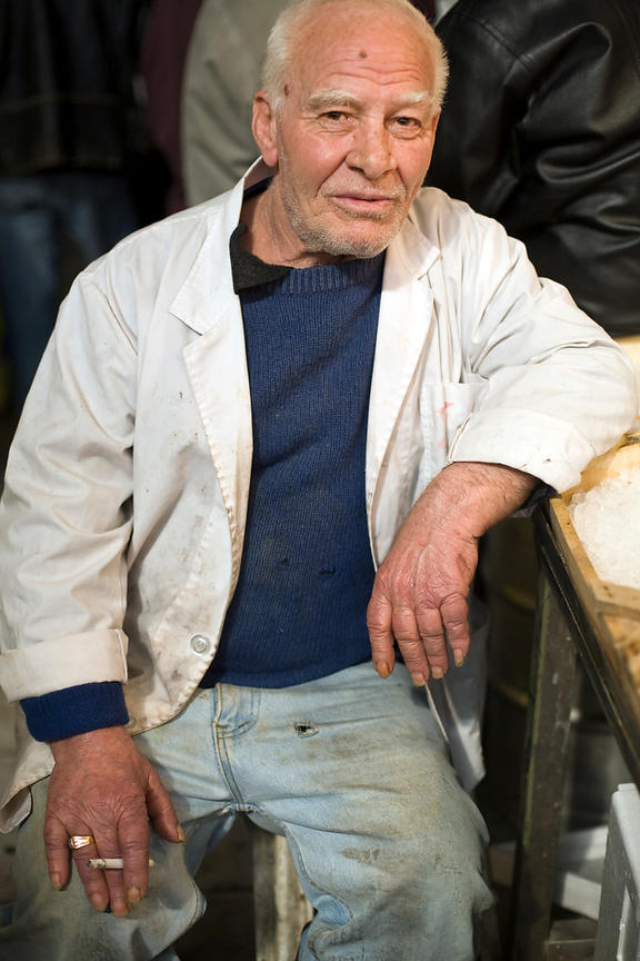 Greece - Athens - An elderly fishmonger pauses to smoke a cigarette by his stall in the Athens Central Market