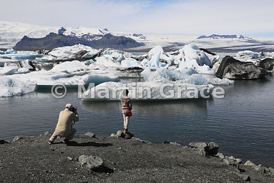 Tourist photographing with icebergs at Jokulsarlon glacier lagoon, Austurland (Eastern Region, East Iceland), Iceland