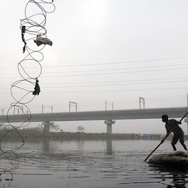 A scavenger looks for discarded waste to sell. Yamuna River, New Delhi, India